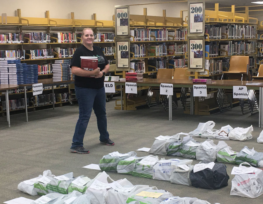 Library Clerk Janna Pearce prepares personalized bags of books for students to take home.