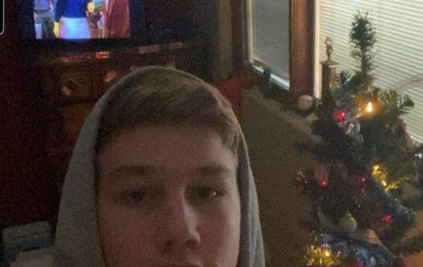 Tyler enjoys watching TV next to his Christmas tree