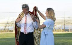Proud mother Kimberly Washburn helps Ben Washburn don his kingly cloak..