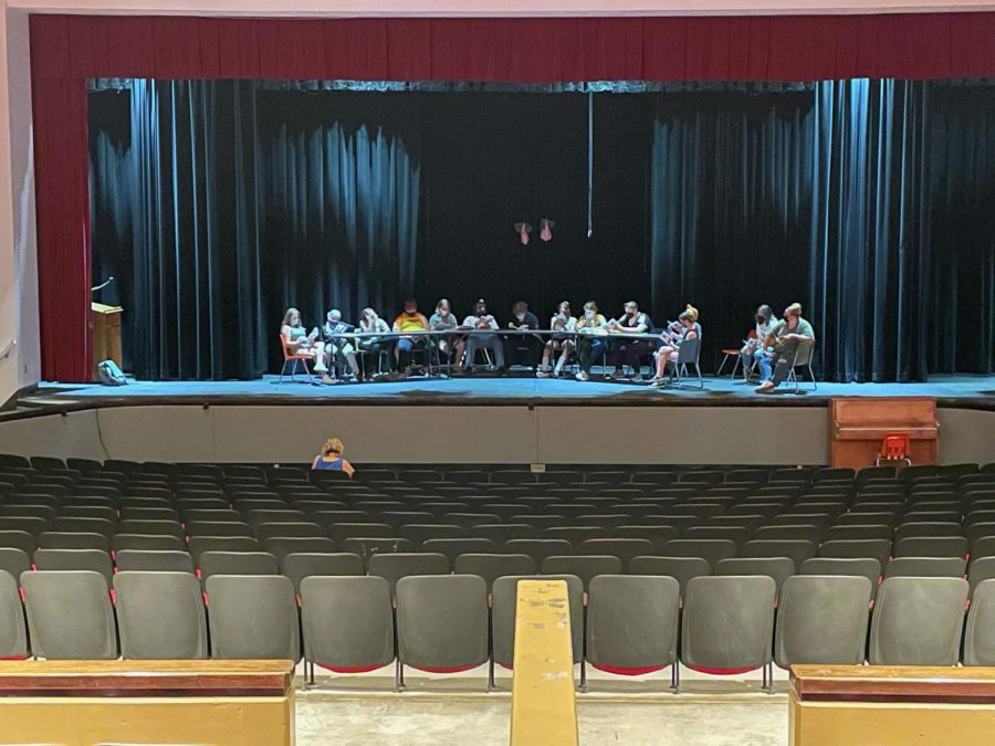 Cast members begin rehearsals on stage.